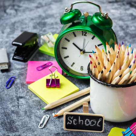 Education, back to school concept. School stationery, supplies, pencil, pen, note, alarm clock on a grunge chalkboard. Selective focus