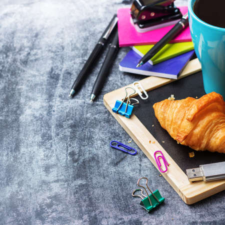 Education, back to school, business office breakfast concept. Stationery, supplies, pencil, pen, note, croissant and mug of black coffee on a grunge chalkboard. Selective focus, copy space background Stock Photo