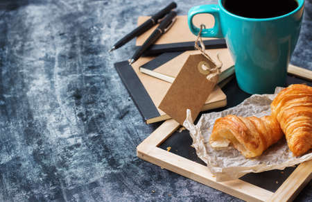 Education, business office breakfast concept. Stationery, supplies, pencil, pen, note, croissant and mug of black coffee on a grunge chalkboard. Selective focus, copy space background