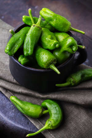 pimiento: Food and drink, still life, moody concept. Raw green peppers pimientos de padron traditional spanish tapas on a black rusty table. Selective focus Stock Photo