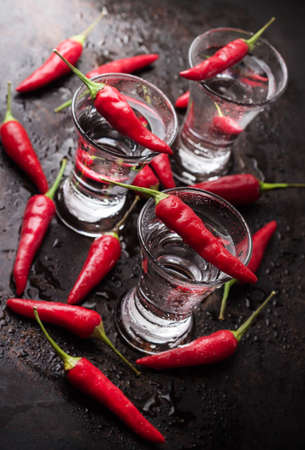 Food and drink, holidays, still life concept. Vodka with chili peppers on rusty grunge table. Selective focus
