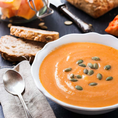 natural moody: Still life, food and drink, seasonal concept. Autumn spicy pumpkin soup in a white bowl with grain cereal bread on a table. Selective focus Stock Photo