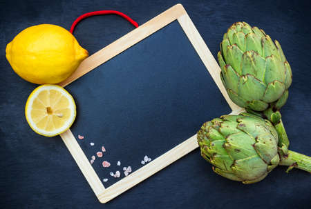moody background: Organic fresh artichokes with lemon with copy space board, grunge moody background. Selective focus, top view overhead flat lay