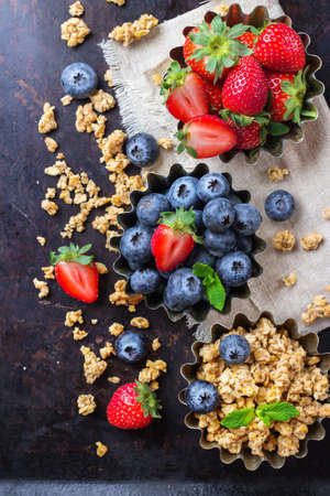 Breakfast, healthy food concept. Homemade muesli granola with berries in a rustic bowl on rusty black table. Selective focus, top view overhead flat lay
