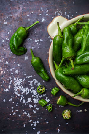 natural moody: Food and drink, still life, moody concept. Raw green mexican spanish peppers jalapeno on a black rusty table. Selective focus, top view flat lay overhead Stock Photo