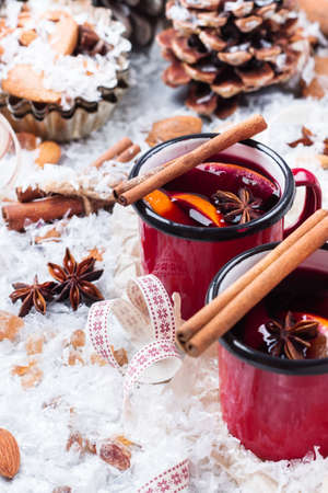 Hot mulled wine in a red mug for winter and fall holidays. Christmas drink in rustic style. Selective focus