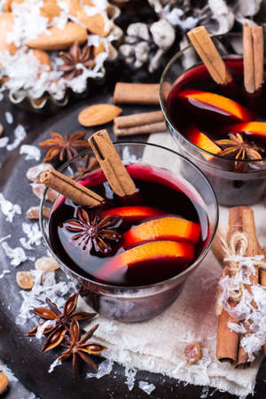 punch spice: Hot mulled wine in a red mug for winter and fall holidays. Christmas drink in rustic style. Selective focus