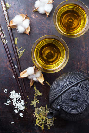 Japanese chinese tea teapot sushi chopsticks rice on a grunge table. Selective focus, top view overhead flat lay