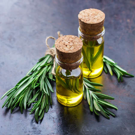 bath essence: Healthy lifestyle concept. Natural rosemary essential oil on a rusty black table for beauty, spa, therapy. Selective focus Stock Photo