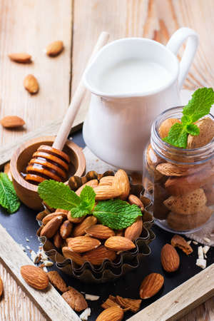 Almond milk in a jug with ingredients for healthy vegetarian vegan breakfast Stock Photo