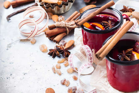 Hot mulled wine in a red mug for winter and fall holidays. Christmas drink in rustic style. Selective focus, copy space background
