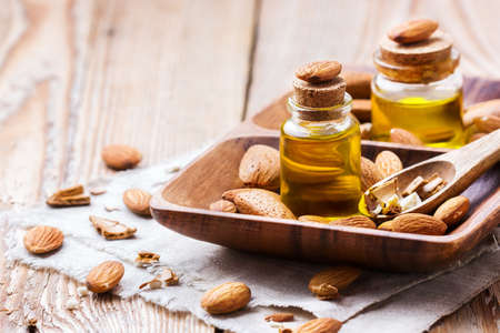 bath essence: Healthy lifestyle concept. Natural sweet almond essential oil, essence in glass bottle on a rustic wooden table for beauty, spa, therapy, bath