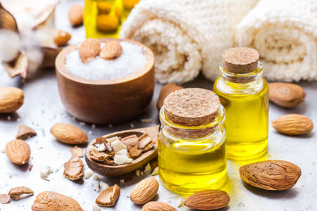 bath essence: Healthy lifestyle concept. Natural sweet almond essential oil, essence in glass bottle with sea salt on a rustic table for beauty, spa, therapy, bath Stock Photo