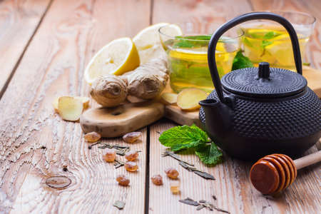 Japanese chinese tea teapot lemon ginger honey on a rustic wooden table. Drink infusion for cold flu winter days