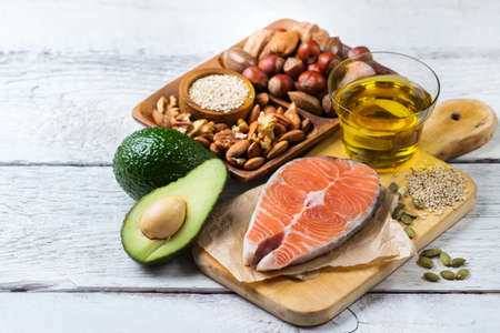 Selection of healthy fat sources food, salmon fish avocado olive oil pumpkin seeds nuts sesame on a white rustic wooden table