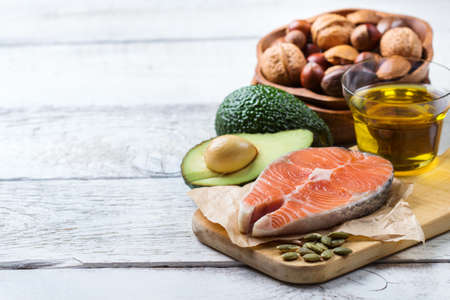 Selection of healthy fat sources food, salmon fish avocado olive oil pumpkin seeds nuts sesame on a white rustic wooden table. Copy space background Standard-Bild