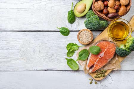 건강 한 지방 소스의 선택 음식, 연어 물고기 아보카도 올리브 오일 호박 씨앗 견과류 브로콜리 녹색 시금치 흰색 소박한 나무 테이블에. 공간을 복사