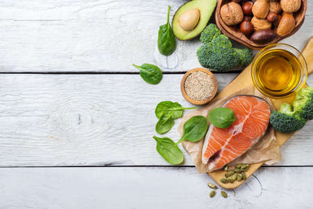 Selection of healthy fat sources food, salmon fish avocado olive oil pumpkin seeds nuts broccoli green spinach on a white rustic wooden table. Copy space background, top view, flat lay overhead Standard-Bild