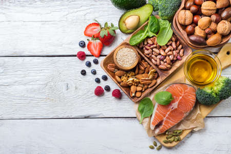 Selection of healthy food for heart, salmon fish avocado olive oil pumpkin seeds nuts broccoli green spinach berries on a white rustic wooden table. Copy space background, top view flat lay overhead