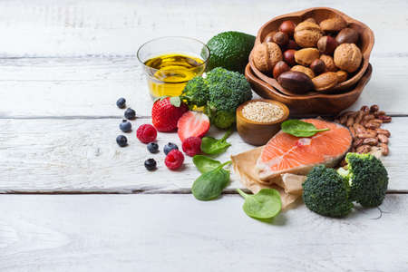 Selection of healthy food for heart, salmon fish avocado olive oil pumpkin seeds nuts broccoli green spinach berries on a white rustic wooden table. Copy space background