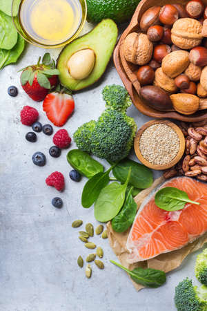 Selection of healthy food for heart, salmon fish avocado olive oil pumpkin seeds nuts broccoli green spinach berries on a white rustic table. Copy space background, top view flat lay overhead
