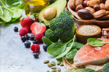 Selection of healthy food for heart, salmon fish avocado olive oil pumpkin seeds nuts broccoli green spinach berries on a white rustic table