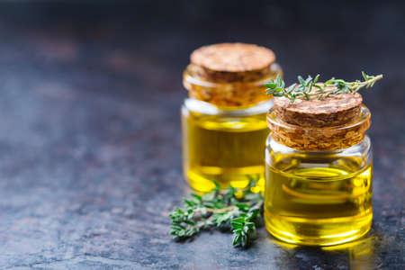 健康と美容、静物の概念。緑の葉と小さなガラスの瓶に有機不可欠なタイムオイルスペースの背景をコピーします。