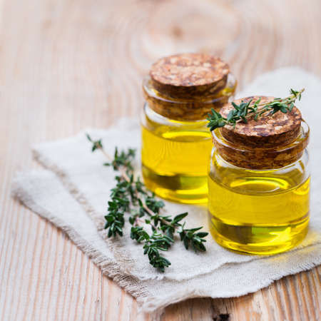 Health and beauty, still life concept. Organic essential thyme oil in a small glass jar with green leaves on a rustic wooden table
