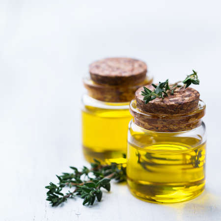 elixir: Health and beauty, still life concept. Organic essential thyme oil in a small glass jar with green leaves on a white rustic wooden table