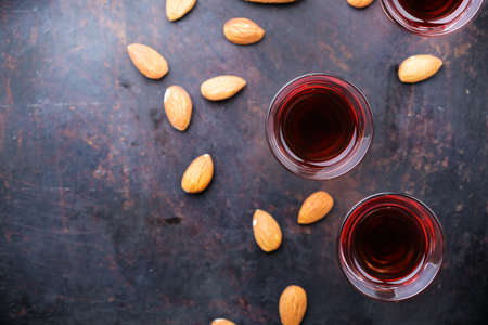 Food and drink, party, alcohol concept. Traditional italian sweet almond liquor amaretto on a grunge black table, digestif beverage, copy space background, top view flat lay overhead Stock Photo