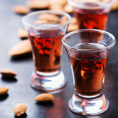 Food and drink, party, alcohol concept. Traditional italian sweet almond liquor amaretto on a grunge black table, digestif beverage