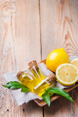 elixir: Health and beauty, still life concept. Organic essential lemon oil in a small glass jar with green leaves and yellow fruit on a rustic wooden table. Copy space background