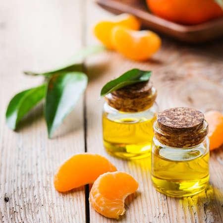 elixir: Salud y belleza, concepto de naturaleza muerta. Aceite esencial de mandarina, mandarina y clementina en un pequeño frasco de vidrio con hojas verdes y fruta de naranja en una mesa de madera rústica