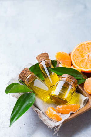 clementine fruit: Health and beauty, still life concept. Organic essential tangerine, mandarin, clementine oil in a small glass jar with green leaves and orange fruit on a rustic table. Copy space background
