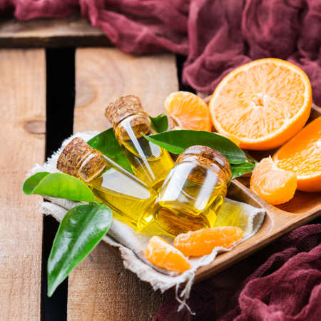 clementine fruit: Health and beauty, still life concept. Organic essential tangerine, mandarin, clementine oil in a small glass jar with green leaves and orange fruit on a rustic wooden table