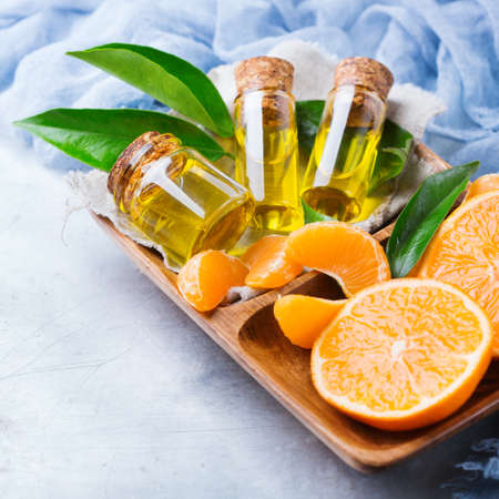 clementine fruit: Health and beauty, still life concept. Organic essential tangerine, mandarin, clementine oil in a small glass jar with green leaves and orange fruit on a rustic table Stock Photo