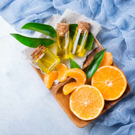 clementine fruit: Health and beauty, still life concept. Organic essential tangerine, mandarin, clementine oil in a small glass jar with green leaves and orange fruit. Top view flat lay overhead