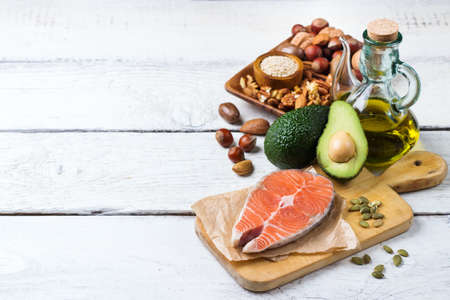 Selection of healthy fat sources food, salmon fish avocado olive oil pumpkin seeds nuts sesame on a white rustic wooden table. Copy space background Archivio Fotografico
