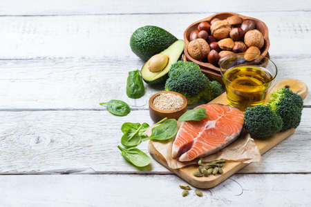 unsaturated: Selection of healthy fat sources food, salmon fish avocado olive oil pumpkin seeds nuts broccoli green spinach on a white rustic wooden table. Copy space background
