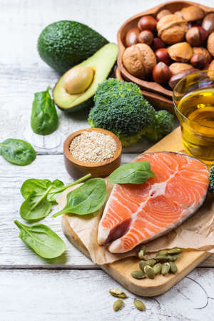 Selection of healthy fat sources food, salmon fish avocado olive oil pumpkin seeds nuts broccoli green spinach on a white rustic wooden table