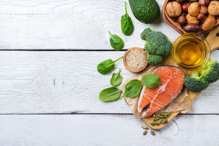 Selection of healthy fat sources food, salmon fish avocado olive oil pumpkin seeds nuts broccoli green spinach on a white rustic wooden table. Copy space background, top view flat lay overhead Stock Photo