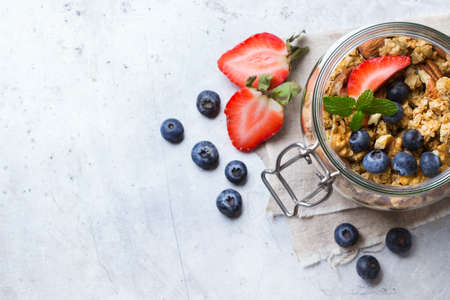 Breakfast, healthy food concept. Homemade muesli granola with berries in a jar on a table. Selective focus, copy space background, top view flat lay overhead