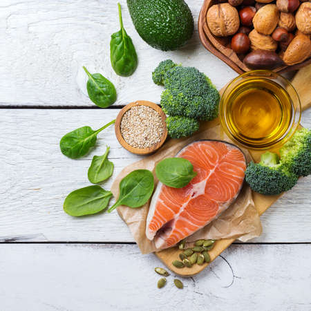 Selection of healthy fat sources food, salmon fish avocado olive oil pumpkin seeds nuts broccoli green spinach on a white rustic wooden table. Flat lay top view overhead