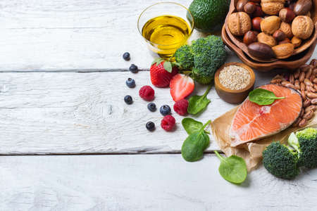 Selection of healthy food for heart, salmon fish avocado olive oil pumpkin seeds nuts broccoli green spinach beans berries on a white rustic wooden table. Copy space background