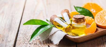 Gesundheit und Schönheit, Stillleben Konzept. Bio ätherisches Mandarine, Mandarine, Clementine Öl in einem kleinen Glas mit grünen Blättern und orange Frucht auf einem rustikalen Holztisch. Kopieren Sie Raum Hintergrund Standard-Bild