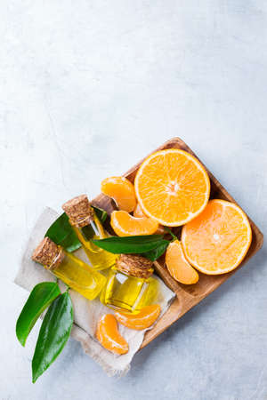 Health and beauty, still life concept. Organic essential tangerine, mandarin, clementine oil in a small glass jar with green leaves and orange fruit on a table. Top view, copy space background Stock Photo