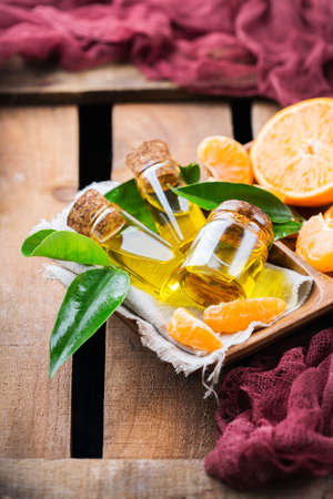 Health and beauty, still life concept. Organic essential tangerine, mandarin, clementine oil in a small glass jar with green leaves and orange fruit on a rustic wooden table