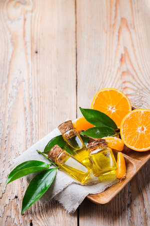 Health and beauty, still life concept. Organic essential tangerine, mandarin, clementine oil in a small glass jar with green leaves and orange fruit on a rustic wooden table. Copy space background Stock Photo