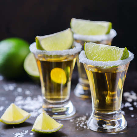 Alcohol, junk food, party, holidays concept. Golden mexican tequila shot on a grunge black table with salt and lime Stock Photo