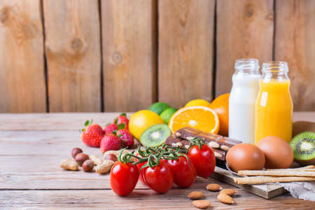 Selection of allergy food, orange citrus juice milk red tomato strawberry kiwi eggs chocolate nuts bread gluten on a rustic wooden table. Copy space background